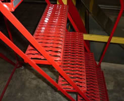 Red safety grating stair treads installed with metal frame in industry